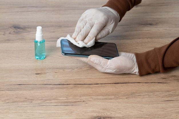 男性は白い手袋を着用し、アルコールを含まない布を使用して、ウイルスを防ぐために携帯電話をきれいにします。