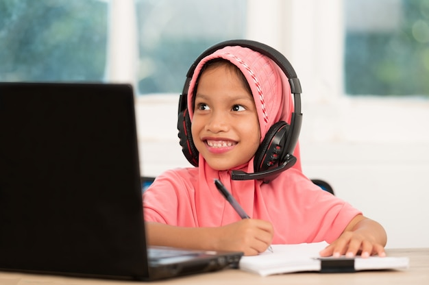 社会的に距離を縮め、伝染病を防ぐために自宅でオンラインで勉強するイスラム教徒の少女