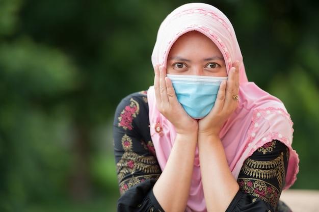 マスクを身に着けている肖像画のイスラム教徒の女性、喜びでカメラを見て