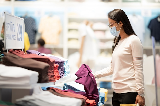 Покупки - главное времяпрепровождение в азиатских регионах. женщина, носящая маску для покупок в универмаге во время вируса короны
