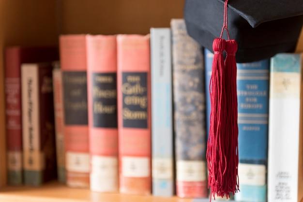 黒の卒業した帽子と赤いタッセルが本に置かれています。