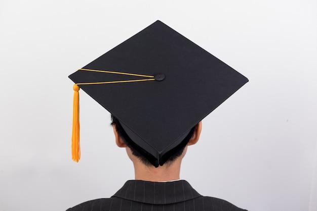孤立したバックグラウンドに黒い帽子をかぶった卒業生の後ろに。