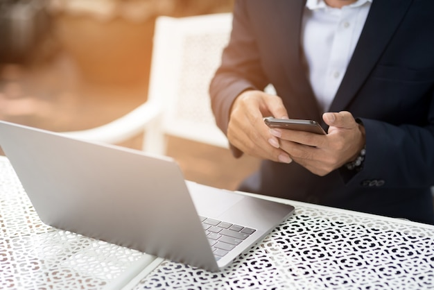 ビジネスマンは、インターネット上の電子メールをチェックするために電話を保持します。