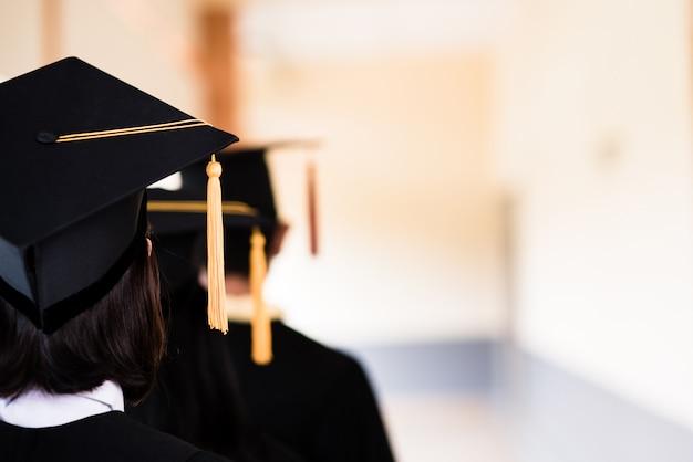 Чернокожие выпускники носят черные костюмы на выпускной в университете.