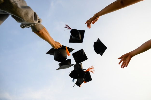 卒業生の黒い帽子を空に投げなさい。