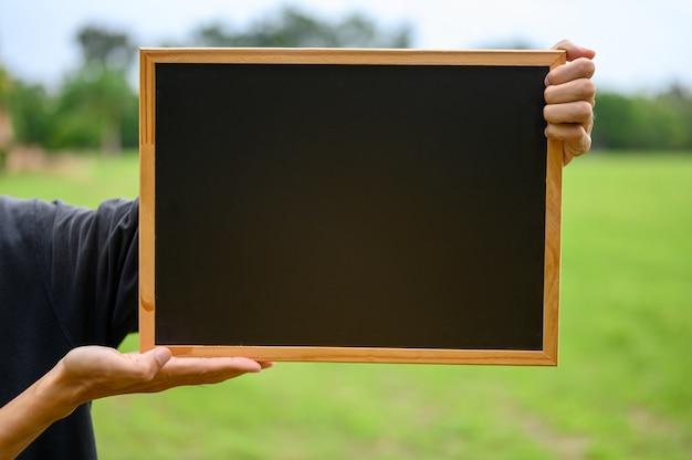 屋外のフィールドで黒板を抱きかかえた