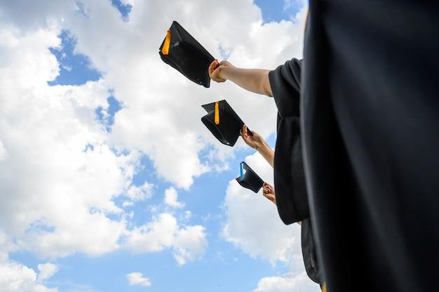 Выпускники бросают шляпы на выпускной в университете.