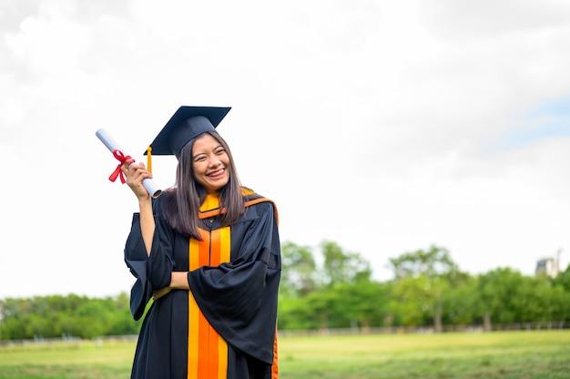 大学で卒業の喜びを表現する黒いフリルのドレスを着ている長い髪の女子学生。