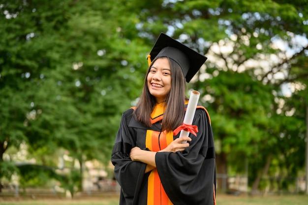 Длинноволосые студентки в черных рюшах одеваются, выражая радость по поводу окончания университета.