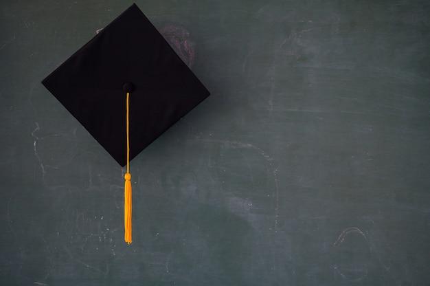 黒の卒業生の帽子が黒板にハング