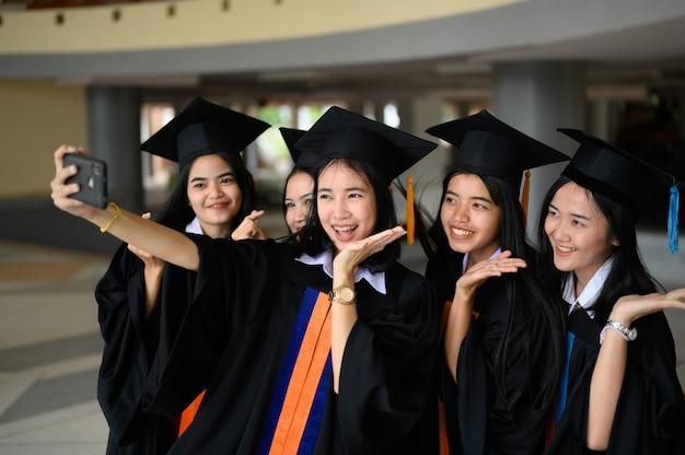 卒業生グループは大学の卒業式で黒い帽子、黒い帽子をかぶった。