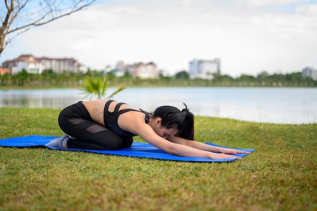 Женщины носят черные, практикующие йогу для здоровья в парке.