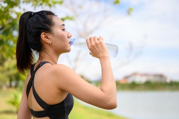 歩いたり走ったりしながら水を飲むために黒い服を着ている女性。