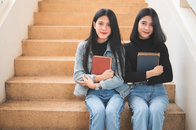 美しい若い学生が大学で勉強するために本を持っています。