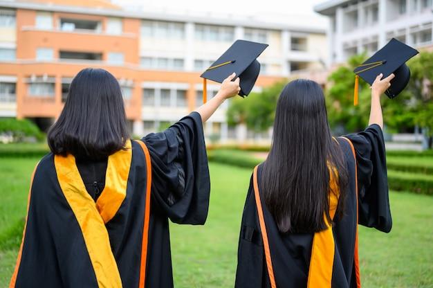 女性の卒業生が大学の卒業式を祝います