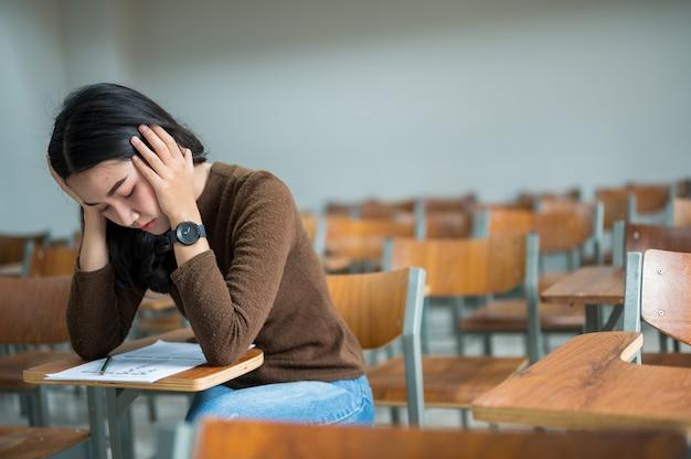 ストレスの多い教室に座っている女子学生