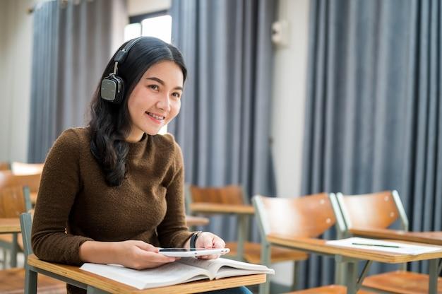 女子学生が座って教室で音楽を聴く
