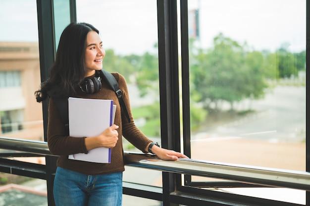 Длинноволосая студентка держит книгу и позирует в университете