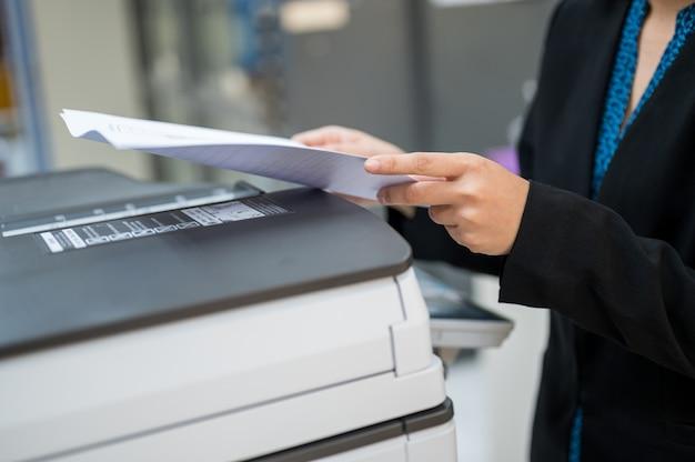 Женский персонал копирует ксерокс в офисе
