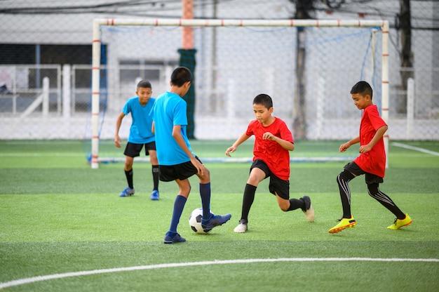 Мальчики играют в футбол на футбольном тренировочном поле