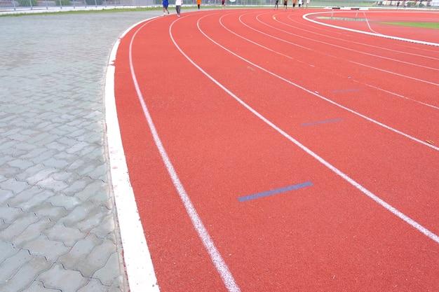 ランニングとジョギングのための赤い床スタジアムの白いトラックライン。