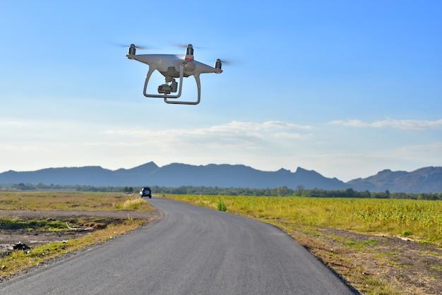 白い無人機は陸上から離陸し、道路の青空の日の上空の写真を撮るため飛行している