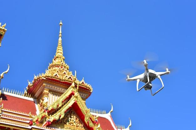 白い無人機が空中写真を撮るためにパビリオン寺院の前を飛行します。