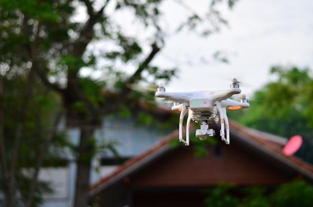 空の写真を撮るために家の前を飛んでいる白飛行船。