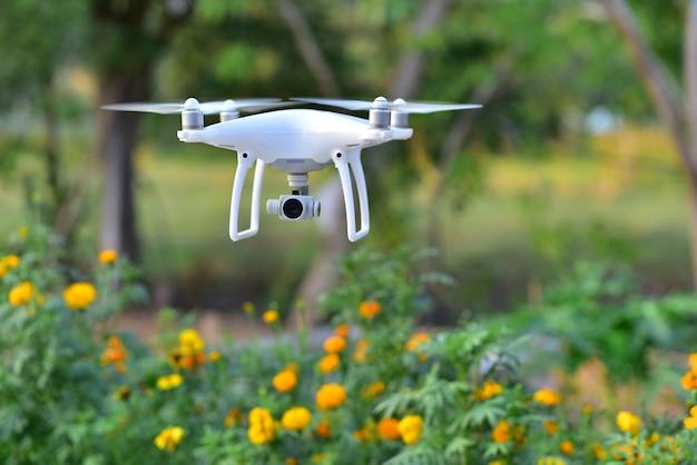 飛行機の写真を撮るために花の庭の上を飛んでくる無人機