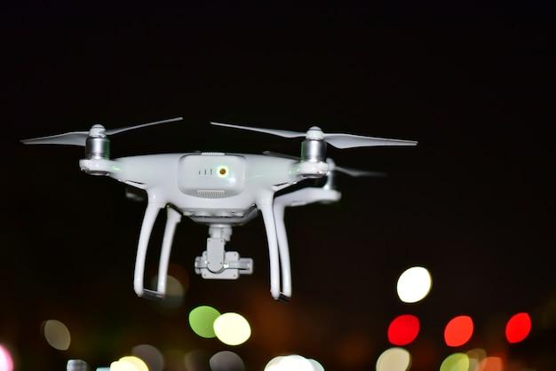 ドローンは夜に空中写真を撮るために土地から離陸ライトカラーボケ