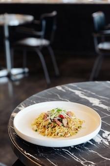 黒大理石のテーブルの上にハムとカニの肉炒め中華麺