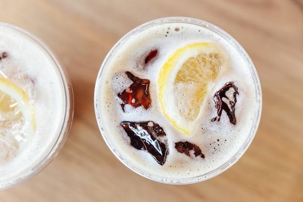 木製のテーブルにレモンとアイスニトロ冷たい醸造コーヒーのトップビュー