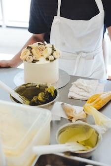 パティシエがステンレス製のカウンターの上に黄色いバターの花の装飾でケーキを作る