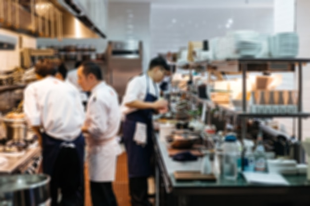 ぼやけたレストランシェフ:スーシェフ(アシスタント)と一緒に近くのキッチンで調理するエグゼクティブシェフ