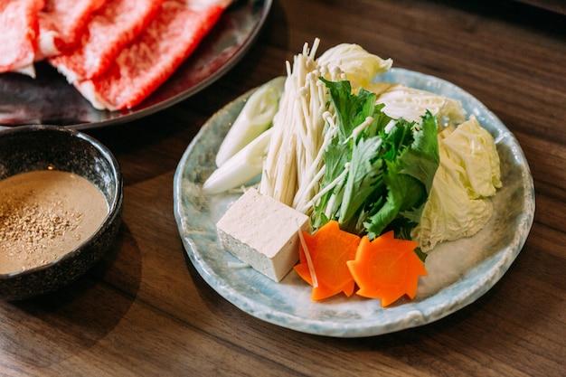 Набор овощей сукияки, включая капусту, ложный пак чой, морковь, шиитаке, энокитаке и тофу.