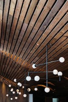 レトロな電球のランプは、暗いオーク材の木製の天井からぶら下がっています。暖かく居心地の良いエレガントなデザイン。