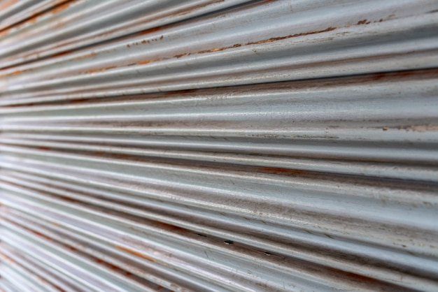 鋼の素朴なヴィンテージの転がり扉。素朴なシャッタードアの質感。
