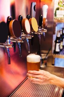 泡から凍ったガラスにビールの栓からクラフトビールを注ぐ男。アルコールの概念