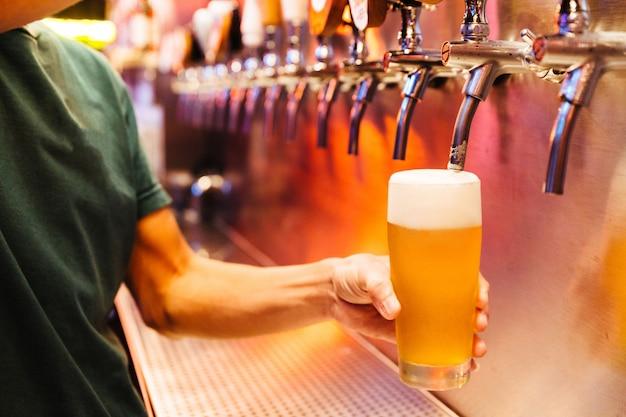 泡から凍ったガラスにビールの栓からクラフトビールを注ぐ男。セレクティブフォーカスアルコールの概念