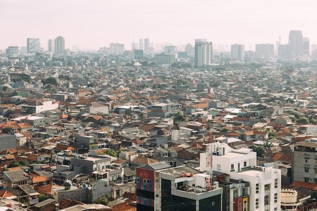 高層ビル、高層ビル、赤いタイルのヒップ屋根地元の建物の霧でジャカルタの街並み。