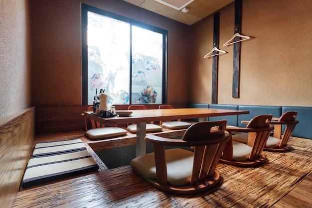 Ресторан рамэн в японском стиле, низкий столик в центре с местами на земле.