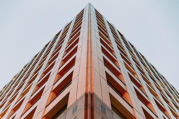 モダンな建物は夕方にバックグラウンドで澄んだ空と下から撮影