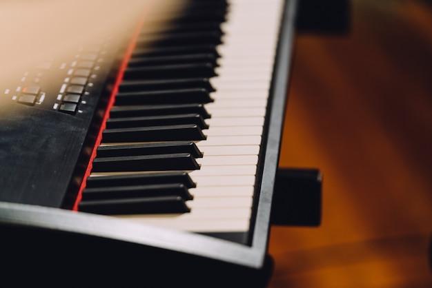 Электронный музыкальный синтезатор клавиатуры с белыми и черными клавишами.