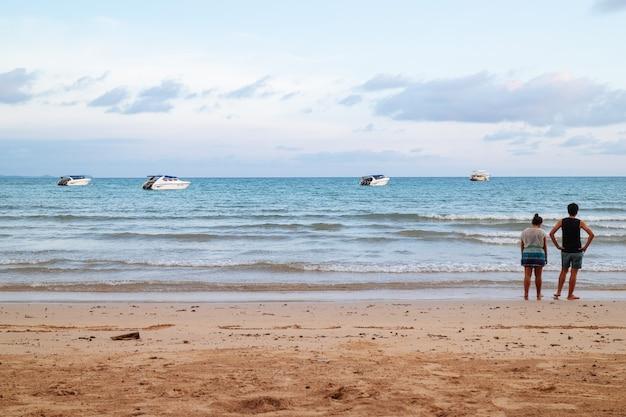 ビーチの上に立って、スピードボートで海を見ているカップルの裏。