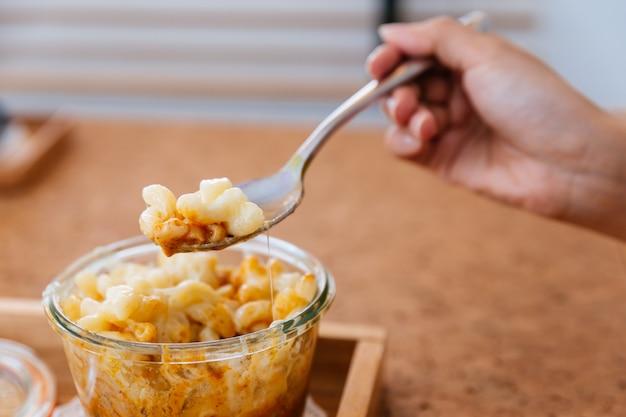女性の手がガラスのボウルにミートソース焼きマカロニチーズをすくいです。