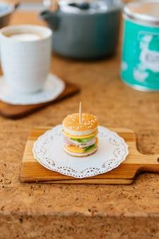 木製のまな板にミニチキンバーガーぼかしティーカップとバックグラウンドでマグカップ。