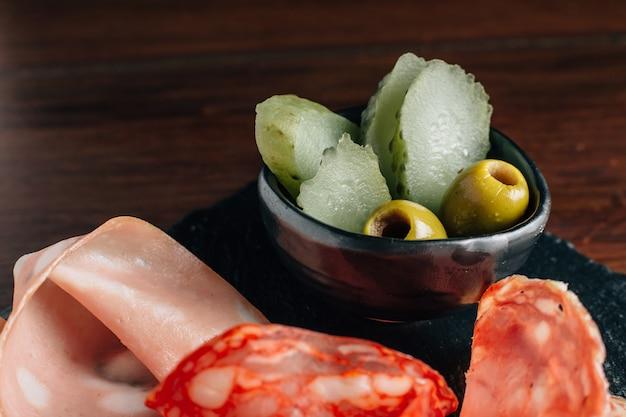 Закройте вверх солений и оливки в черной чашке с колбасами на черной каменной плите.