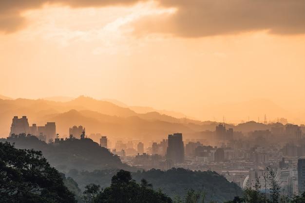 台北の街並みと太陽が沈む夕日の山々。
