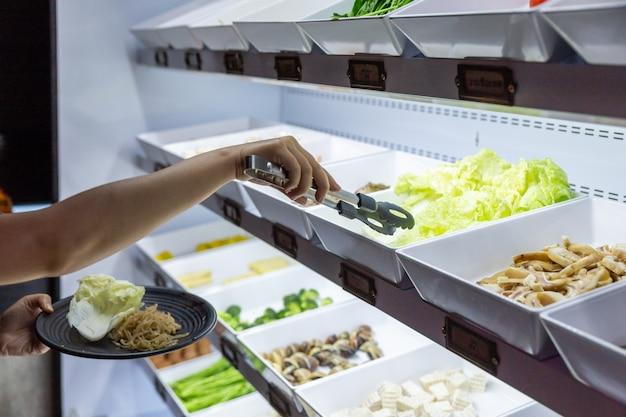 手の選択と黒のプレートで新鮮な野菜をつまんで