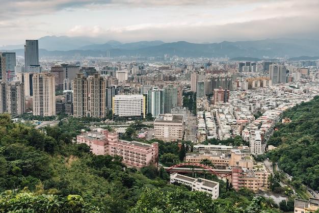 バックグラウンドで山の層を持つ台北のダウンタウンの空中パノラマ